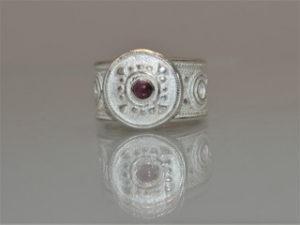 Anello in argento con due fasce laterali sulle quali si posa un bottone con pietra centrale. Decrescente nella parte in inferiore e aperto per adattarsi a varie misure