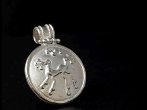 Ciondolo in argento tondo del diametro 2.5 cm e altezza 3.3 cm dovuta al gancio. Rappresenta una chimera sannita che decorava lo scudo corazza del guerriero